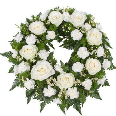 Round funeral wreath with seasonal flowers